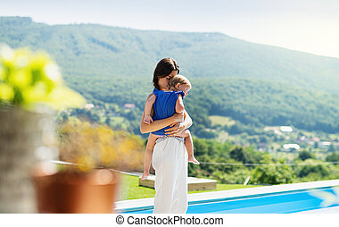 Young mother holding small daughter outdoors in backyard garden.