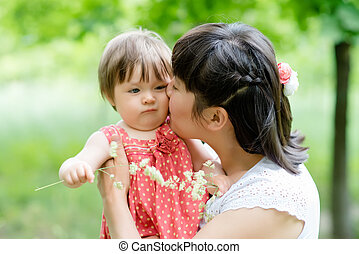 young mother holds daughter on hands