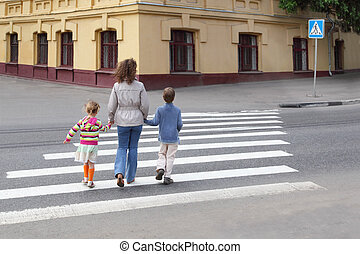 young mother holds hand of little daughter and son and ...