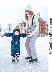 Young mother holds hand of son for boy for 2-3 years, ice skating rink winter in city park. Concept first lesson skating support and support, help parents learning sports activities active lifestyle.