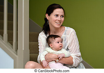 Young mother holds her baby at home