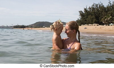 young mother holds in arms little daughter in shallow sea water