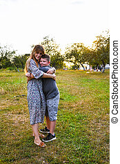 Young mother hugging and kissing her son in summer or autumn park. Family love first. Happy family of mother and child on field at the sunset