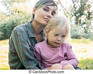 Young mother hugging her daughter three years. Family on a picnic