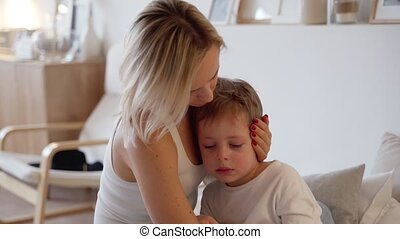 young mother hugs a crying boy in the bedroom