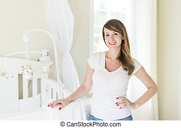 Young mother in baby room at home