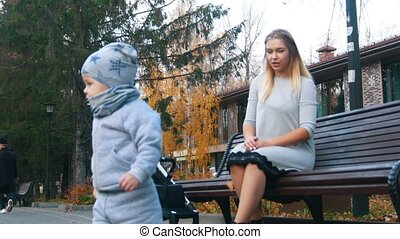 Young mother in dress sitting on the bench. Her little baby son walking on sidewalk
