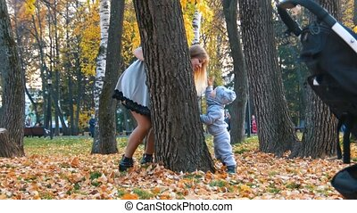 Young mother in dress with her little baby playing hide n...