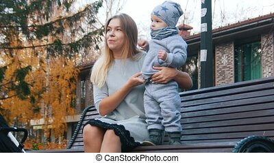 Young mother in dress with her little baby sitting on the bench in autumn park and playing.