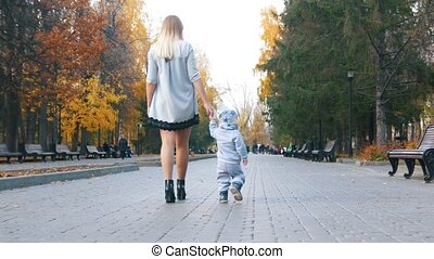 Young mother in dress with her little baby walking in the autumn park holding hands
