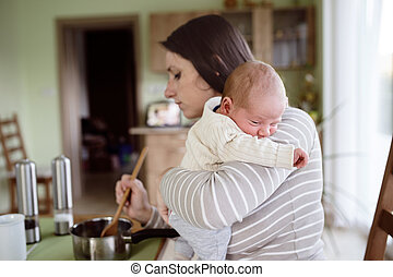 Young mother in kitchen holding baby son, cooking