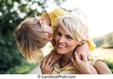 Young mother in nature giving small daughter a piggyback ride.