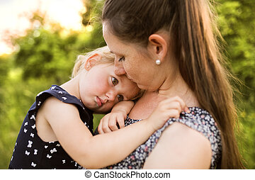 Young mother in nature holding little daughter in the arms....
