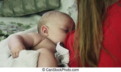 Young mother in red shirt breastfeeding little crying baby in towel. Motherhood.