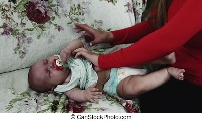 Young mother in red shirt dress up crying baby on sofa. Motherhood. Care.