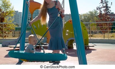 Young mother is pushing baby boy on a swing