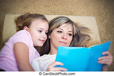 Young mother is reading a book to her daughter.