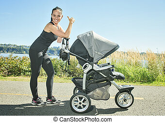 Young mother jogging with a baby buggy - A Young mother...