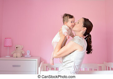 Young mother kisses her baby