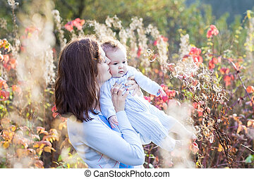 Young mother kissing her baby daughter on a walk in a sunny autu