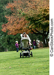 Young mother leaning over a pushchair or stroller