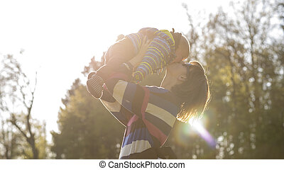 Young mother lifting her baby in the air giving him a kiss