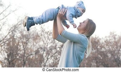 Young mother lifts up on hands her little baby son. Happy family
