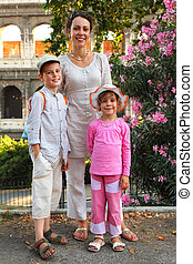 young mother, little son and daughter are near Colosseum in Rome