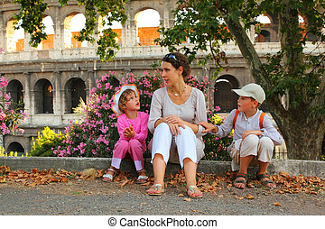 young mother, little son and daughter sitting near Colosseum in Rome and talking, focus on mother