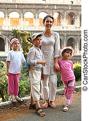 young mother, little son and two daughters are near Colosseum in Rome, focus on boy