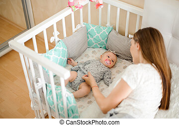 Young mother lulling cute little newborn baby girl in bed