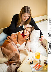 mother lying next to sick daughter in bed