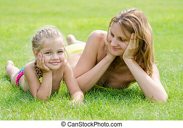 Young mother lying on green grass and looking at his five-year daughter who is lying near