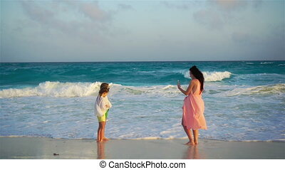 Young mother making photo on phone of her kids at the beach in soft evening light