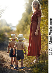 Young mother on the country walk with her sons