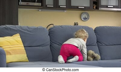 Young mother play hide and seek under sofa with her cute toddler daughter.