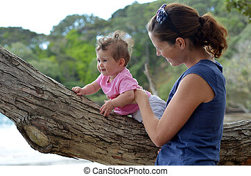 Young mother play outdoor with her baby