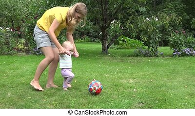 young mother play with baby girl with ball in summer garden. 4K