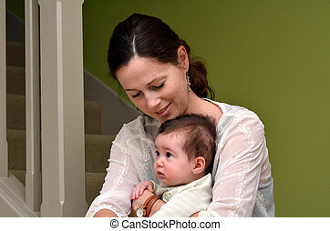 Young mother play with her baby at home