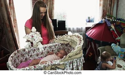 Young mother play with little baby lie in cute crib. Motherhood. Boy at sofa.