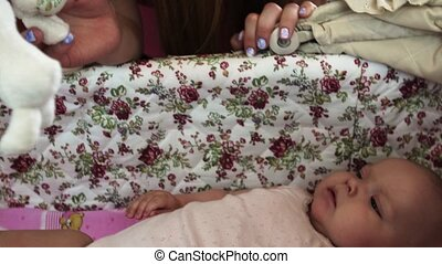 Young mother play with little baby lie in cute crib. Motherhood. Happiness.