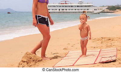young mother play with little daughter at mat on beach