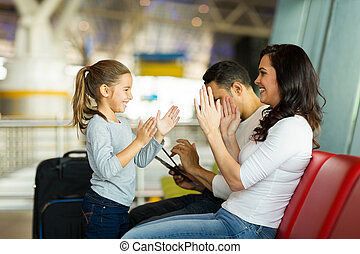 young mother playing a game with daughter at airport - happy...