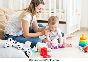 Young mother playing on floor with her baby boy at living room