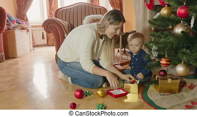 Young mother playing with baby boy under Christmas tree at living room