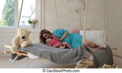 Young mother playing with baby daughter in bed