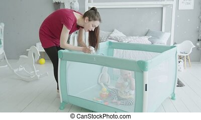 Young mother playing with baby sitting in playpen