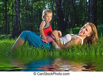 Young mother playing with  daughter on grass