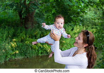 Young mother playing with her adorable baby in a park