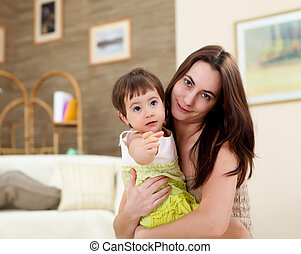 young mother playing with her baby at home